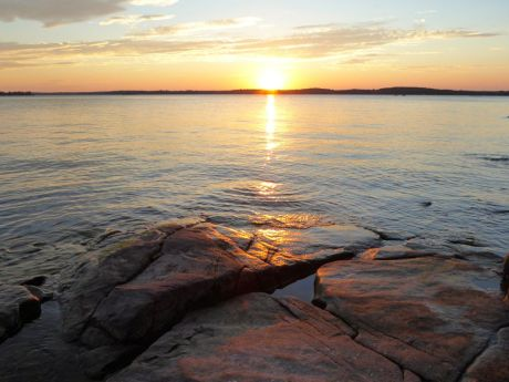 Just before sunset the light hits the rocks along the shore on Morgan Island. —  Kring Point, New York